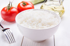 Freshly brewed rice, tomatoes and olive oil. Freshly brewed rice on a wooden table Stock Image