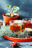 Freshly brewed tea in glass cup on blue background. Orange hot drink, selective focus. Fresh herbal tea with tincture of red berri Stock Image
