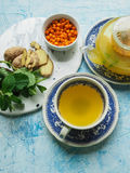 Freshly brewed tea in a glass pot of sea-buckthorn berries, mint and ginger Royalty Free Stock Photo