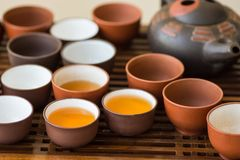 Freshly brewed tea poured in ceramic cups pot utensils on wooden bamboo dripping tray. Chinese Japanese ceremony. Lifestyle Stock Photography