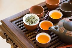 Freshly brewed tea poured in ceramic cups pot utensils on wooden bamboo dripping tray. Loose leaves. Chinese Japanese ceremony Stock Images