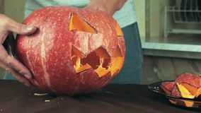 Freshly carved jack o lantern pumpkin in male hands on kitchen table Halloween theme close up shot stock video footage