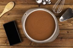 Freshly chocolate cake ready to be baked and smartphone royalty free stock photos