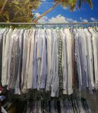 Freshly cleaned men`s shirts and ladies blouses in a textile cleaning. Hanging on hangers and packed in plastic wrap royalty free stock photos