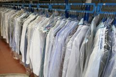 Freshly cleaned men`s shirts and ladies blouses in a textile cleaning. Hanging on hangers and packed in plastic wrap royalty free stock photography