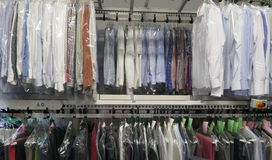 Freshly cleaned men`s shirts and ladies blouses in a textile cleaning. Hanging on hangers and packed in plastic wrap stock images