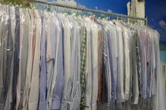 Freshly cleaned men`s shirts and ladies blouses in a textile cleaning. Hanging on hangers and packed in plastic wrap stock photos