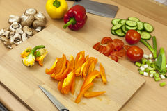 Freshly cleaned and sliced orange bell pepper on a chopping boar. Freshly cleaned and sliced orange bell pepper laying on a wodden chopping board aside a Royalty Free Stock Photos