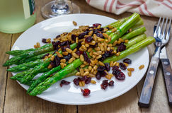 Freshly cooked asparagus appetizer with pine nuts and cranberries Stock Photography