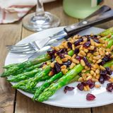 Freshly cooked asparagus appetizer with pine nuts and cranberries on white plate, square format Royalty Free Stock Photography