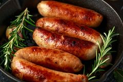 Freshly cooked butchers made, homemade sausages with rosemary in cast iron frying pan royalty free stock photos