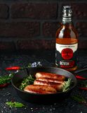 Freshly cooked butchers sausages in skins in cast iron frying pan with Sanford orchards apple cider, Devon, United royalty free stock photo