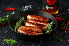 Freshly cooked butchers sausages in skins in cast iron frying pan with Sanford orchards apple cider, Devon, United stock photos