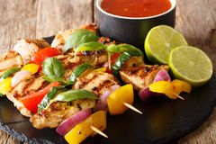 Freshly cooked grilled chicken skewers with vegetables with sauce and lime closeup. horizontal. Freshly cooked grilled chicken skewers with vegetables with sauce royalty free stock photography