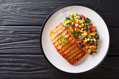 Freshly cooked grilled salmon filet with pepper, corn, blueberry. And onion salad close-up on a plate on a table. horizontal top view from above royalty free stock photos