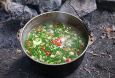 Freshly cooked hot soup in sooty cauldron at camping. Outdoor cooking Royalty Free Stock Photos