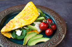 Freshly cooked omelette. Filled with feta cheese, spinach, avocado and tomato. A healthy vegetarian breakfast served on a rustic plate on a stone slate table Royalty Free Stock Photos