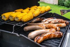 Freshly cooked sausages on a grill with corn close-up. Background of sausages made with charcoal Stock Images