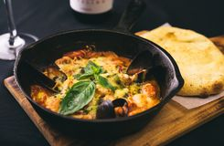 Freshly cooked seafood. Clams with cheese in tomato sauce in metal pan on cutting board Royalty Free Stock Photography