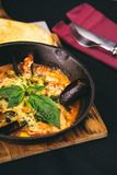 Freshly cooked seafood. Clams with cheese in tomato sauce in metal pan on cutting board Stock Photo