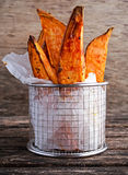 Freshly cooked sweet organic potato fries in paper wrap executed in a serving metal basket on old wooden table royalty free stock photography