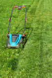 Freshly cut grass strips and blue lawnmower Stock Photos