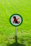 Freshly cut green grass with round sign forbidding dogs. No dogs allowed royalty free stock photo