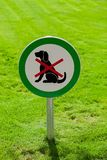 Freshly cut green grass with round sign forbidding dogs. No dogs allowed stock images