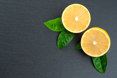 Freshly cut half lemons with leaves on black stone. Copy space Royalty Free Stock Images