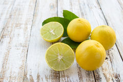 Freshly cut half and whole lemons on white wooden table Stock Images