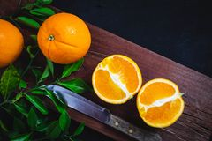 Freshly cut orange fruit on a wooden cutting board.Black backgr royalty free stock image