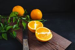 Freshly cut orange fruit on a wooden cutting board.Black backgr stock photo