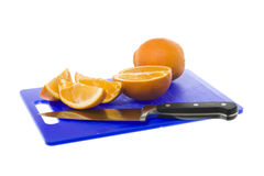 Freshly cut orange pieces on chopping board. With knife and isolated background Stock Photography