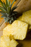 Freshly cut pinapple pieces. Fresh organic pinapple pieces on a wooden cutting board Royalty Free Stock Image