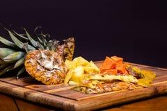 Freshly cut pineapple and papaya on a wood cutting board. stock photo