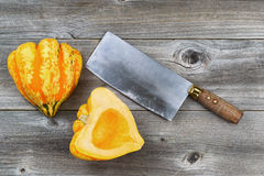 Freshly cut squash with large knife on rustic wood Royalty Free Stock Image