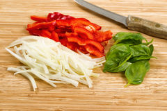 Freshly cut vegetables ready to cook on bamboo cutting board. Close up front view of freshly sliced red pepper, white onion, and large basil leafs with cutting Royalty Free Stock Photo