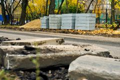 Freshly dug up old curbstones on the foreground and new ones standing on the background. Road curb replacement on the Moscow street in Autumn. Broken freshly dug stock photo