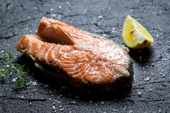 Freshly fried salmon served with dill and lemon. On black rock Stock Photo