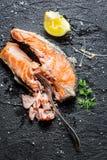 Freshly fried salmon served with lemon. On black rock Royalty Free Stock Photo