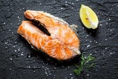 Freshly fried salmon served on a rock. Freshly fried salmon served on a black rock Stock Images