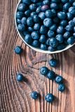 Freshly gathered blueberries put into ceramic bowl. Some fruits freely scattered. On old wooden table. Shot from above Stock Photography