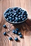Freshly gathered blueberries put into ceramic bowl. Some fruits freely scattered. On old wooden table Royalty Free Stock Photo