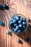 Freshly gathered blueberries put into jar. Some fruits freely  scattered on old wooden table. Shot from above Stock Photos