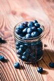 Freshly gathered blueberries put into jar. Some fruits scattered. Freshly gathered blueberries put into jar. Some fruits freely scattered on old wooden table Royalty Free Stock Photos