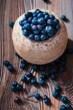 Freshly gathered blueberries put into old ceramic bowl. Some fruits freely scattered on old wooden table. Shot from above Royalty Free Stock Image