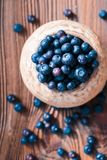 Freshly gathered blueberries put into old ceramic bowl. Some fruits freely scattered on old wooden table. Shot from above stock photos