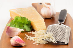 Freshly grated parmesan cheese on a wooden board Stock Photos