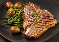 Freshly grilled T bone steak. And vegetables on dark plate Stock Photo