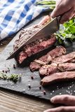 Freshly grilled tomahawk steak on slate plate with salt pepper rosemary and parsley herbs. Chef with knife cuts juicy bovine steak. Freshly grilled tomahawk royalty free stock image